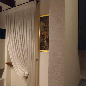 Il tessuto Agena a fili intrecciati per le tende raccolte con bracciali in rame brunito in un interno classico e moderno. Mariano Tende Verona.