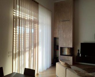 Le onde del lino tinto in bianco e tabacco light per un attico con soffitti travati e pavimenti in legno