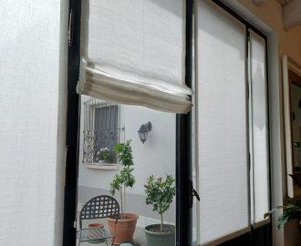 Le tende a pacchetto in tessuto di lino, panama e metallo per le vetrate all'interno di un antico fienile. Mariano tende Verona.
